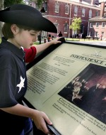 A young boy reads about Independence Hall, where the Declaration of Independence was adopted in 1776. The Independence National Historical Park attracts more than 3 million visitors a year. AP Photo/Rusty Kennedy