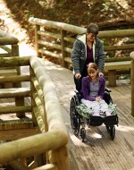 Sarah and Becky Metz cross a wheelchair-accessible wooden bridge at Camp Arrowhead in Barboursville, West Virginia. AP Photo/The Herald-Dispatch/Mark Webb